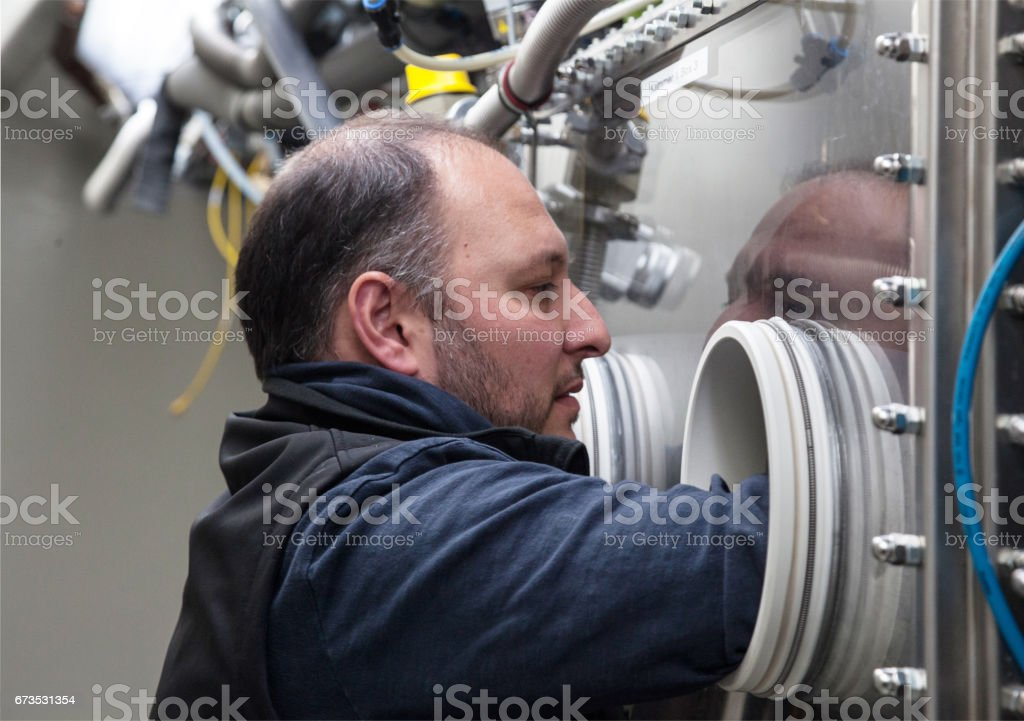 Scientist in lab testing materials in glove box stock photo