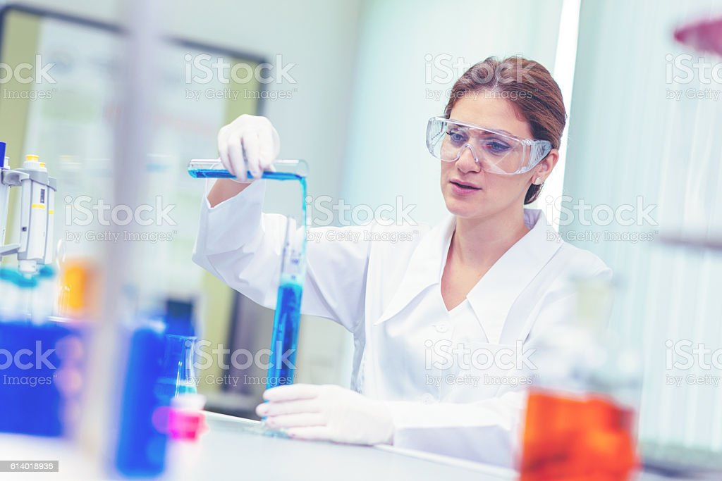 Scientist in laboratory testing chemicals stock photo