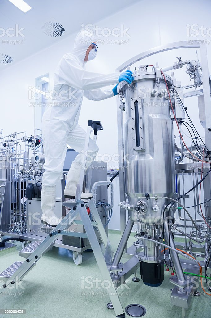 Scientist in protective suit standing on ladder stock photo
