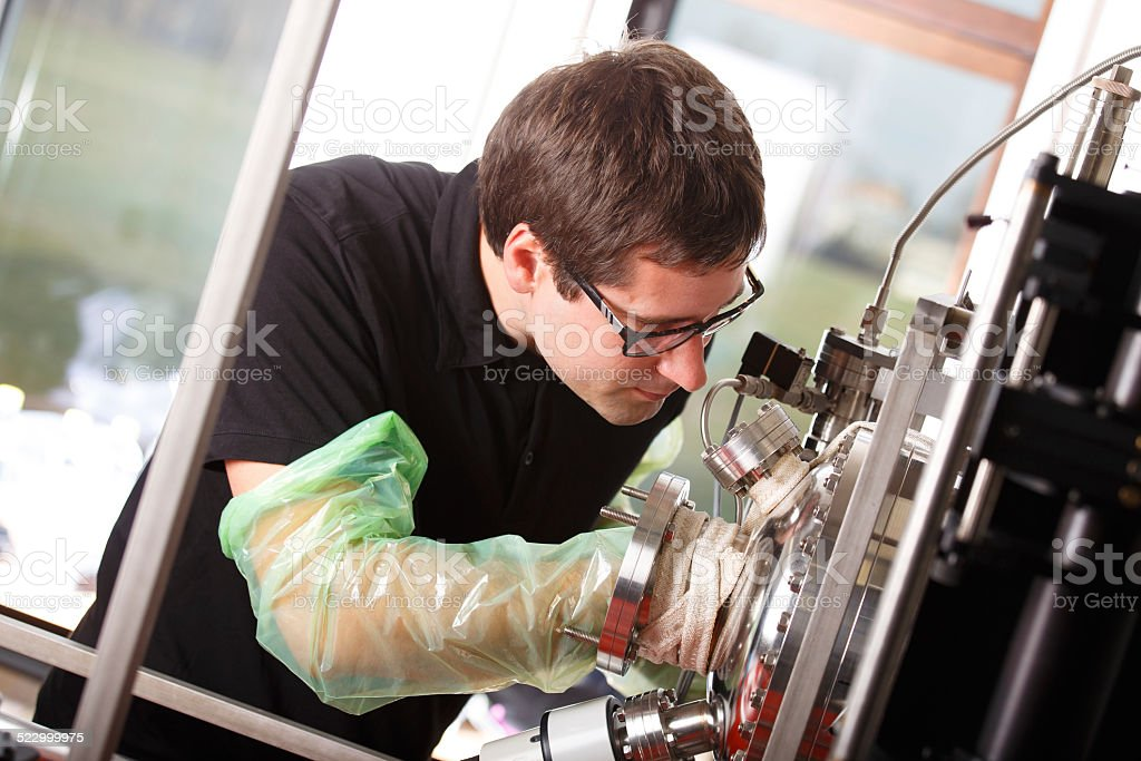 Scientist inserts hand laser deposition chamber stock photo