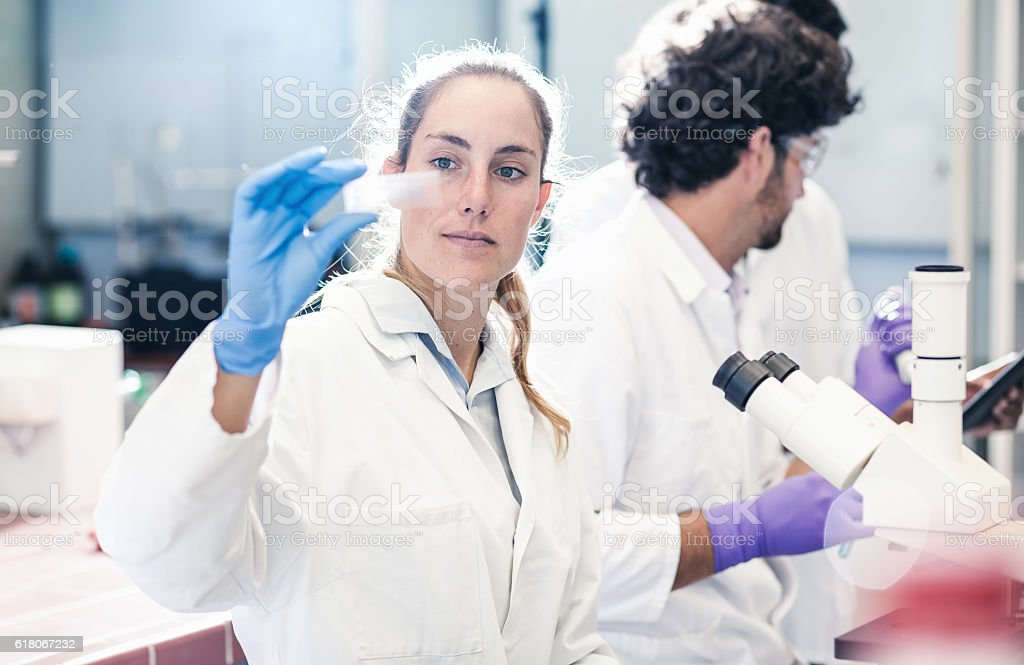 Scientist Looking at a Microscope Slide stock photo
