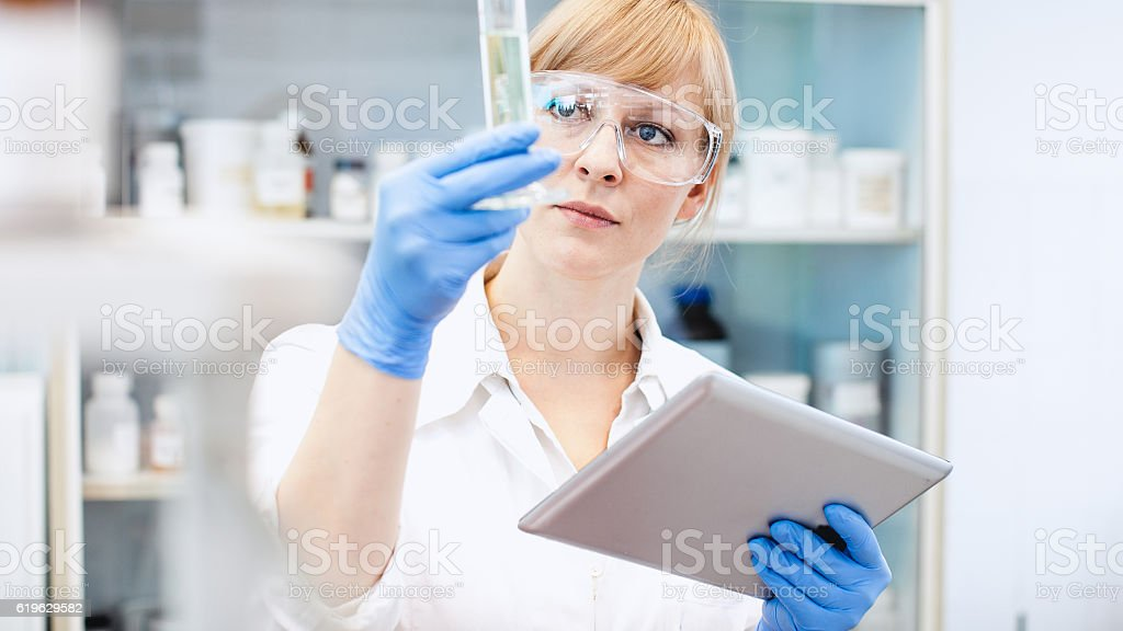 Scientist Looking at Measuring Cylinder,  Holding a Tablet stock photo