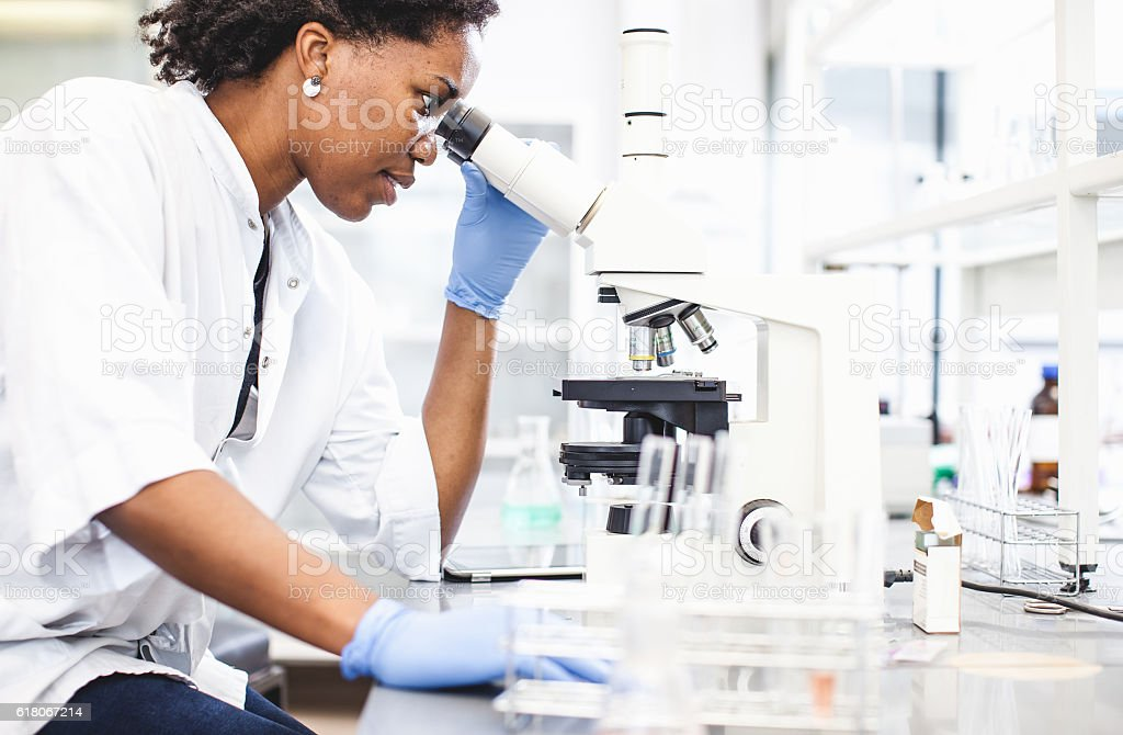 Scientist Looking into the Microscope stock photo
