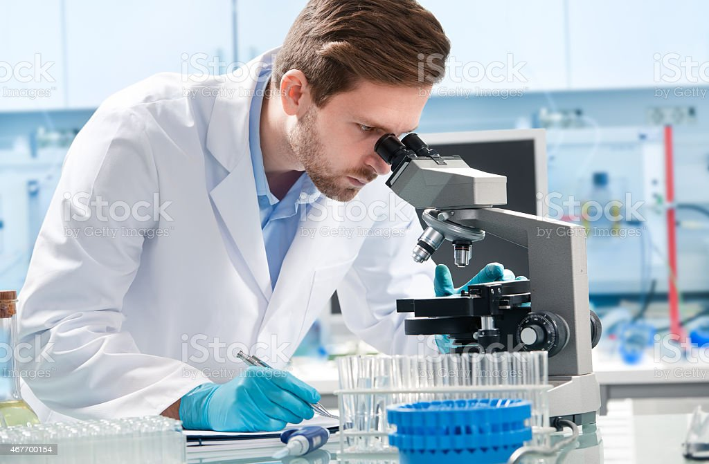 Scientist looking through a microscope stock photo
