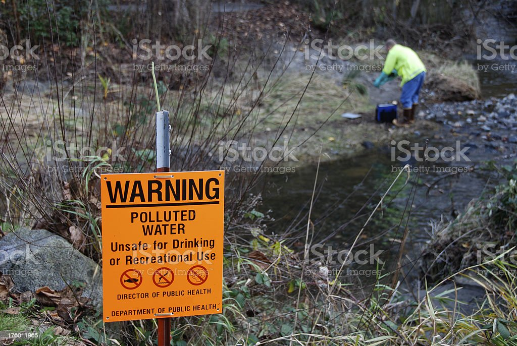 Scientist measuring pollutants in stream royalty-free stock photo
