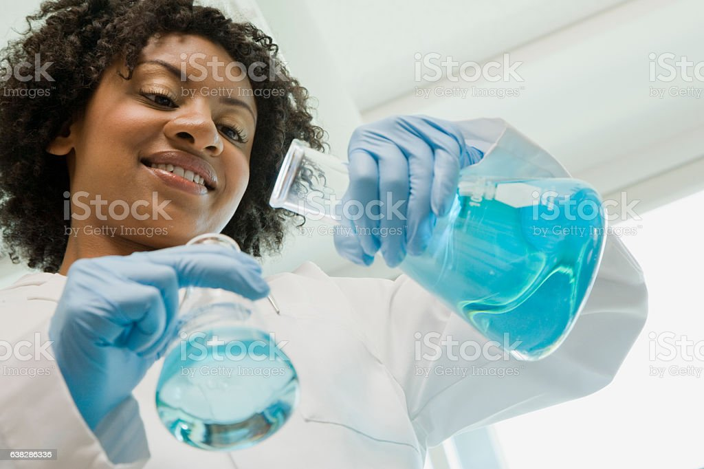 Scientist mixing chemicals in laboratory stock photo