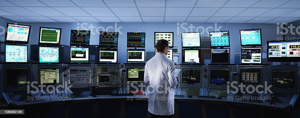 Scientist monitoring computers in control room stock photo