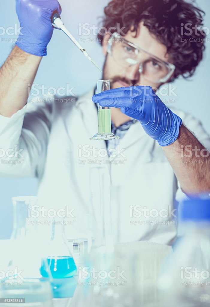 Scientist Pipetting into a Measuring Cylinder stock photo