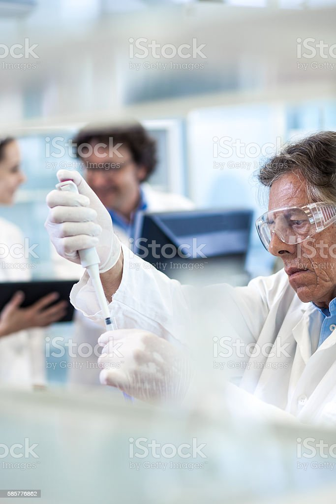Scientist Pipetting Into a Test Tube stock photo