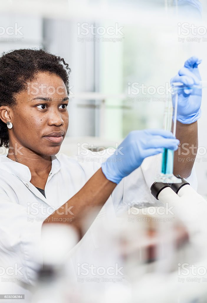 Scientist pouring a chemical into a measuring cylinder stock photo