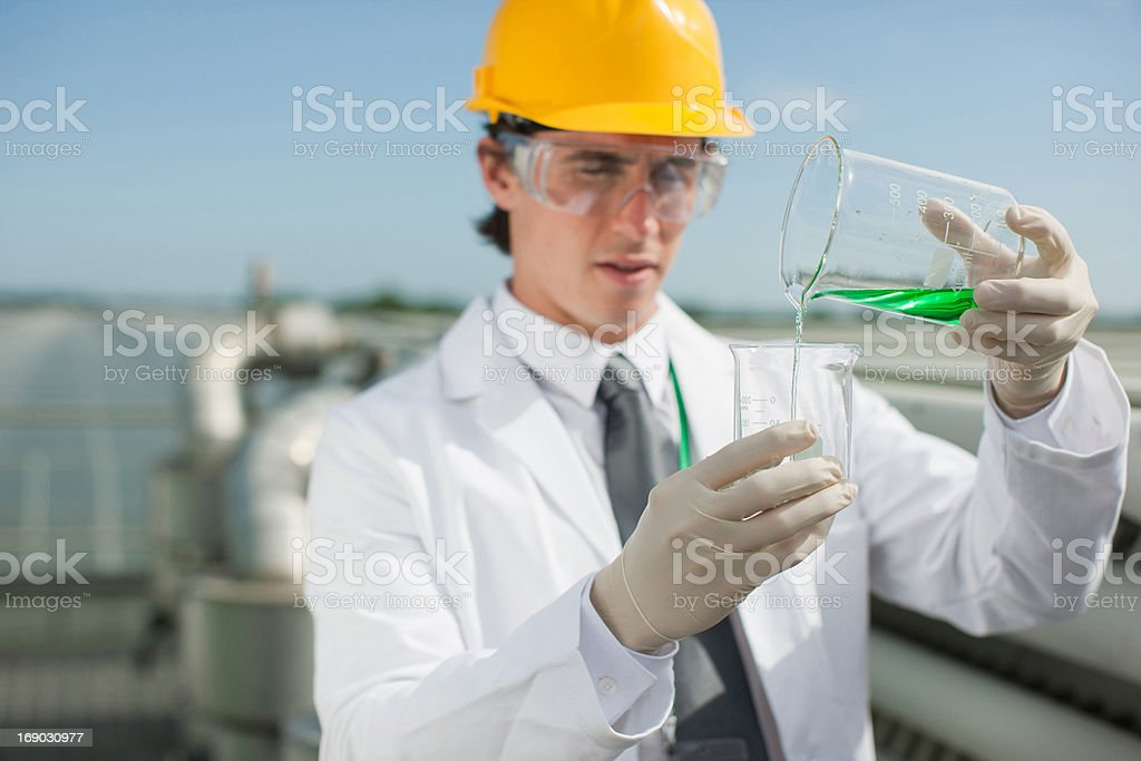 Scientist pouring liquid into beaker outdoors royalty-free stock photo