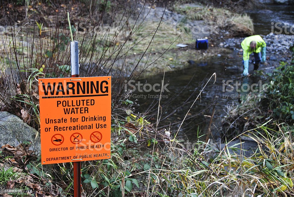 Scientist sampling creek's polluted water stock photo