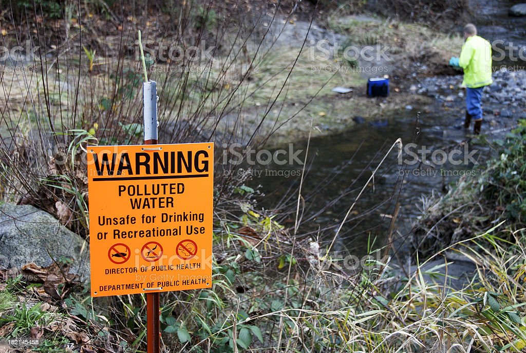 Scientist sampling pollution levels in creek stock photo