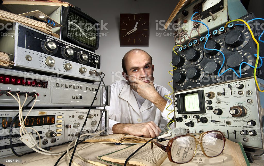 Scientist sitting between vintage electrical equipment stock photo
