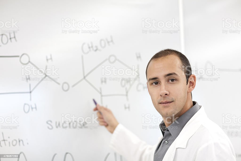 Scientist standing by the white board covered with formulas royalty-free stock photo