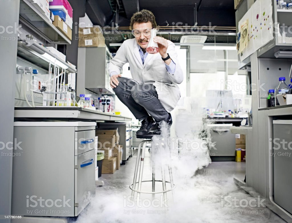 Scientist standing on chair after an explotion stock photo