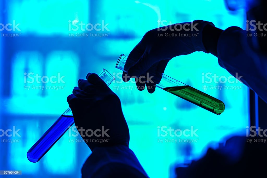 Scientist transferring chemicals between test tubes. stock photo