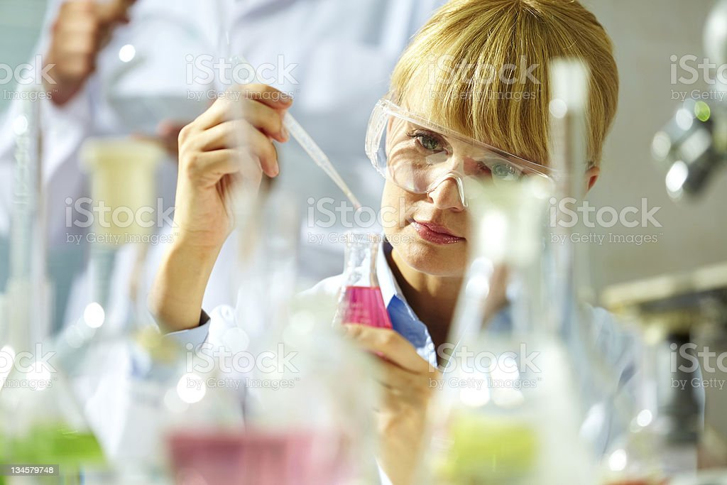 A scientist using a pipette to add liquid to a bottle stock photo
