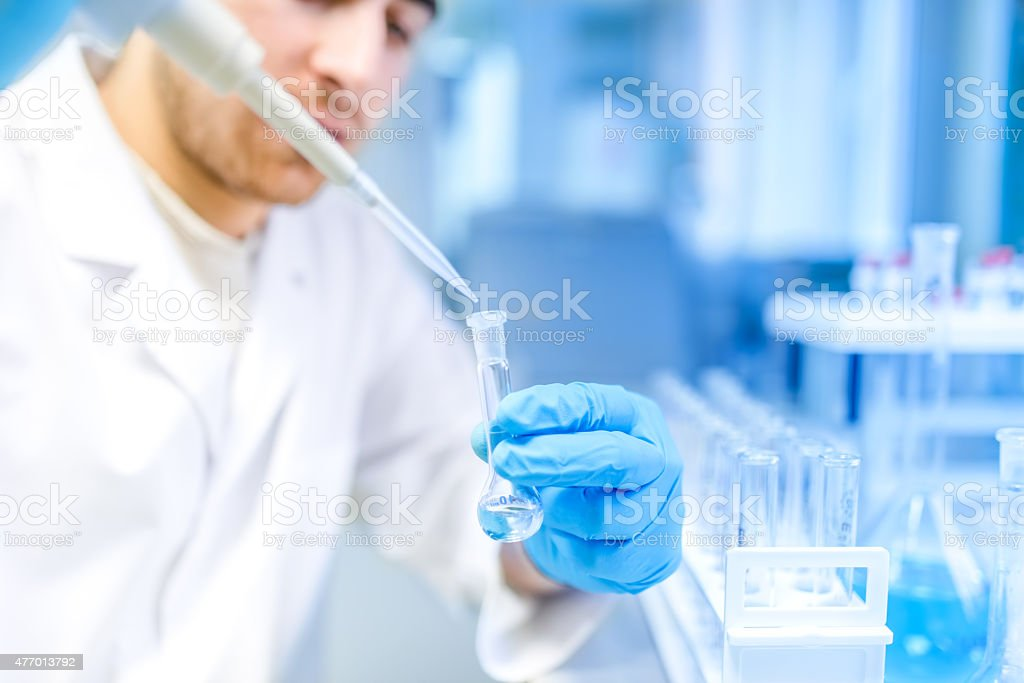 scientist using medical tool for extraction of liquid, in laboratory stock photo