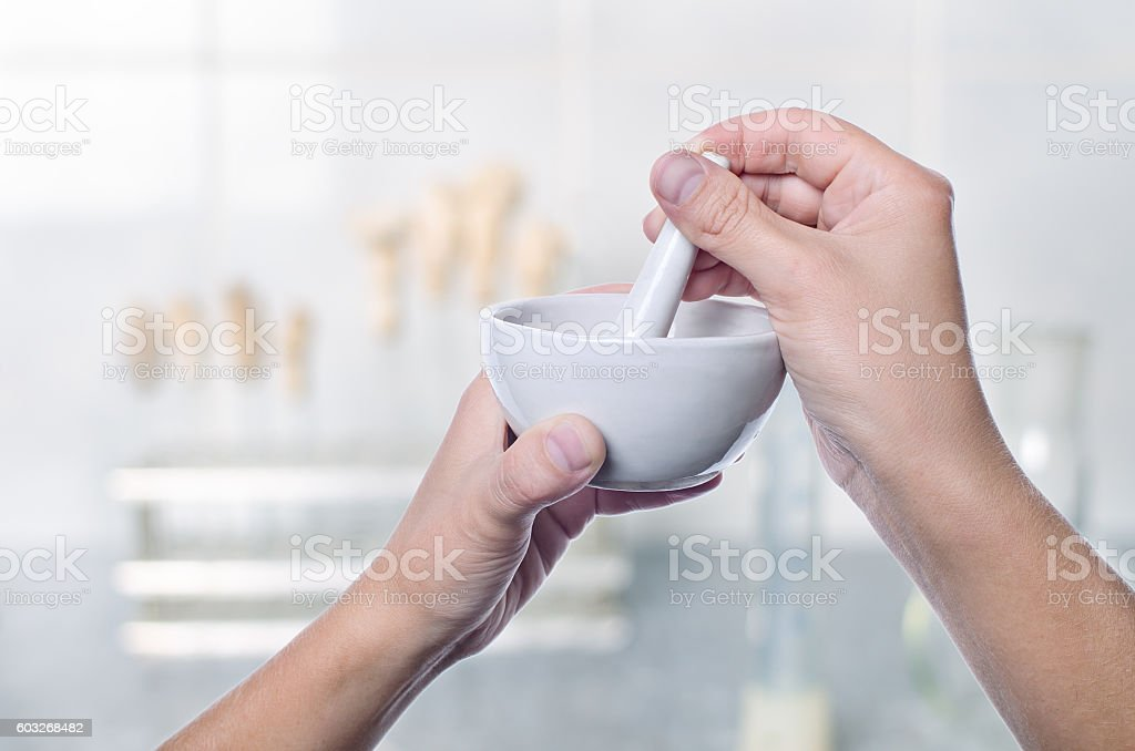 Scientist using pestle and mortar in laboratory stock photo