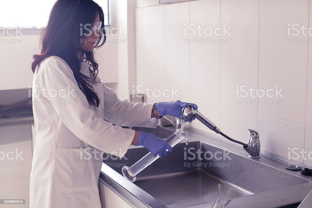 Scientist washing her glass tubes stock photo