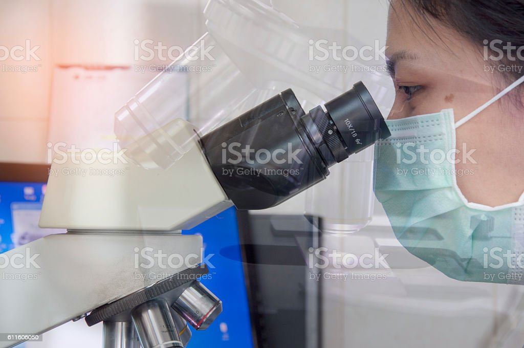Scientist with microscope in laboratory. stock photo