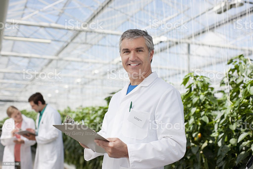 Scientist writing on clipboard in greenhouse royalty-free stock photo