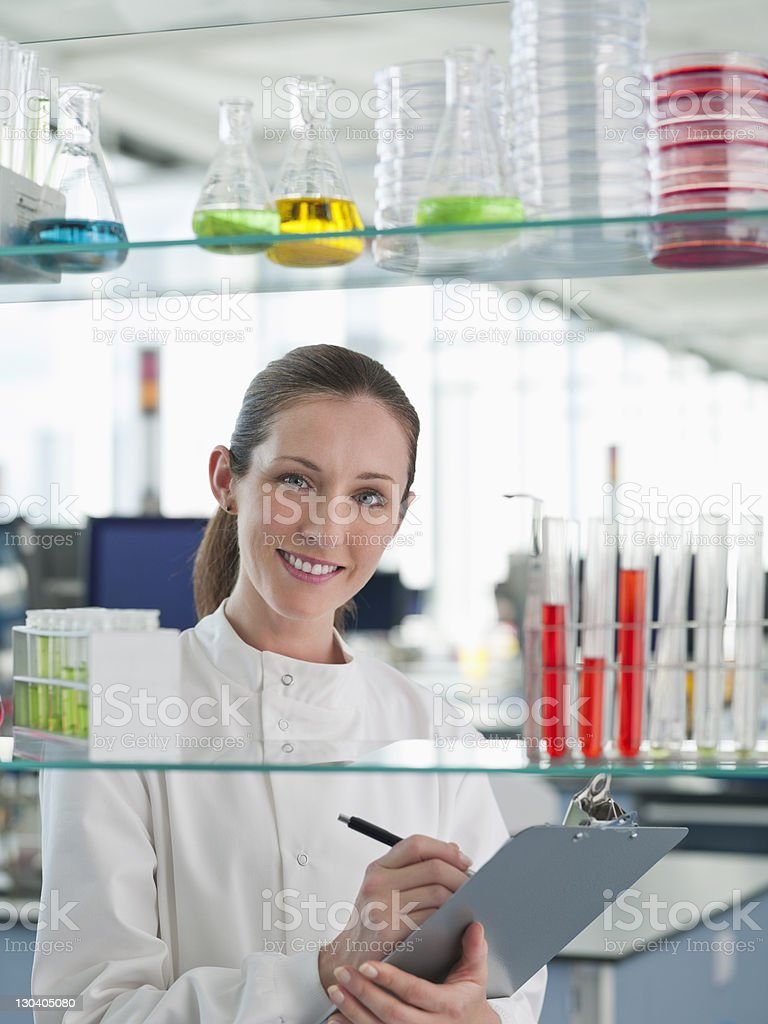 Scientist writing on clipboard in lab royalty-free stock photo