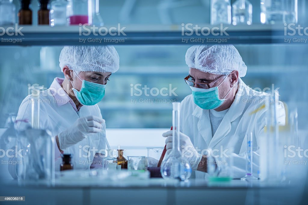Scientists analyzing chemical substances for a new research. stock photo