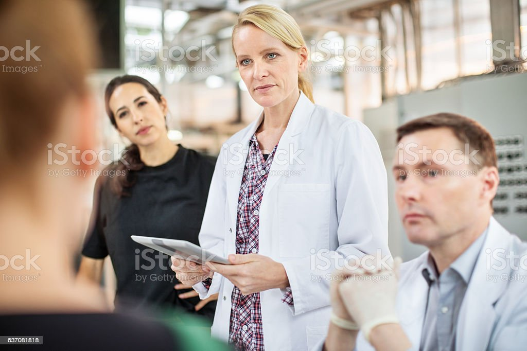 Scientists and farm workers meeting in greenhouse stock photo