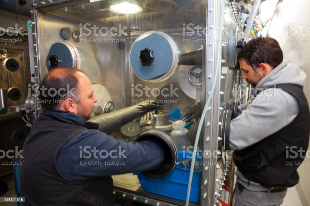 Scientists in lab testing materials in glove box stock photo