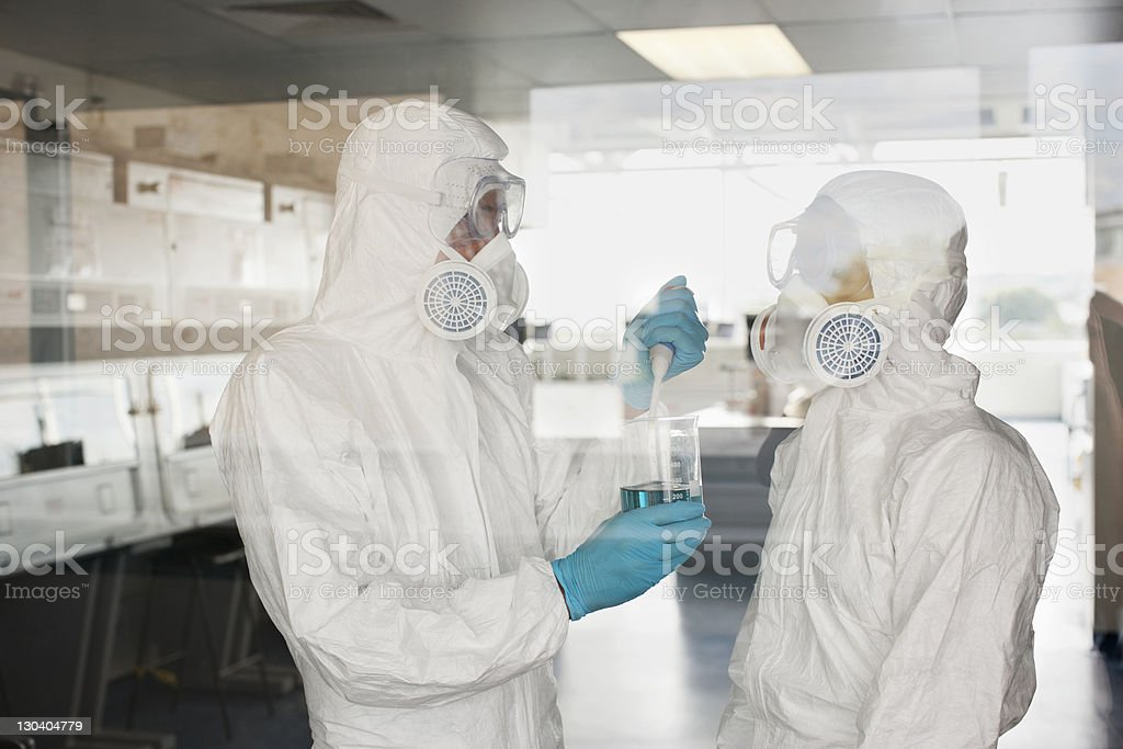 Scientists in protective gear putting liquid in beaker in lab stock photo
