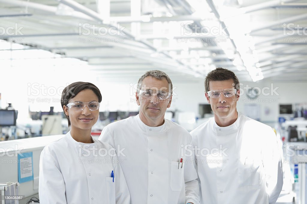 Scientists in protective glasses smiling in lab royalty-free stock photo