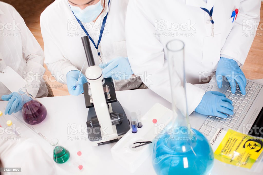 Scientists in research laboratory. Chemicals, laptop, microscope. stock photo