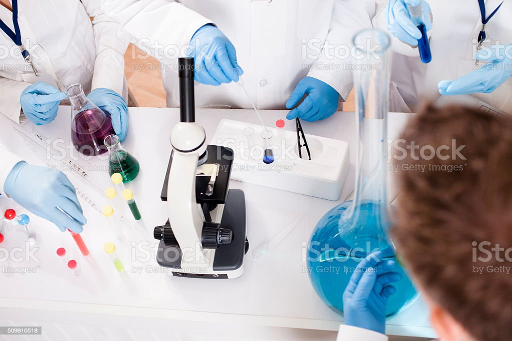 Scientists in research laboratory. Chemicals, microscope. stock photo