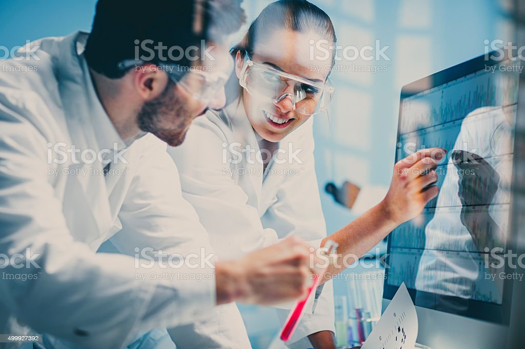 scientists looking at a DNA sequence on the monitor stock photo
