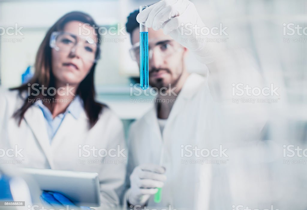 Scientists Looking at a Test Tube Filled With Dilution stock photo