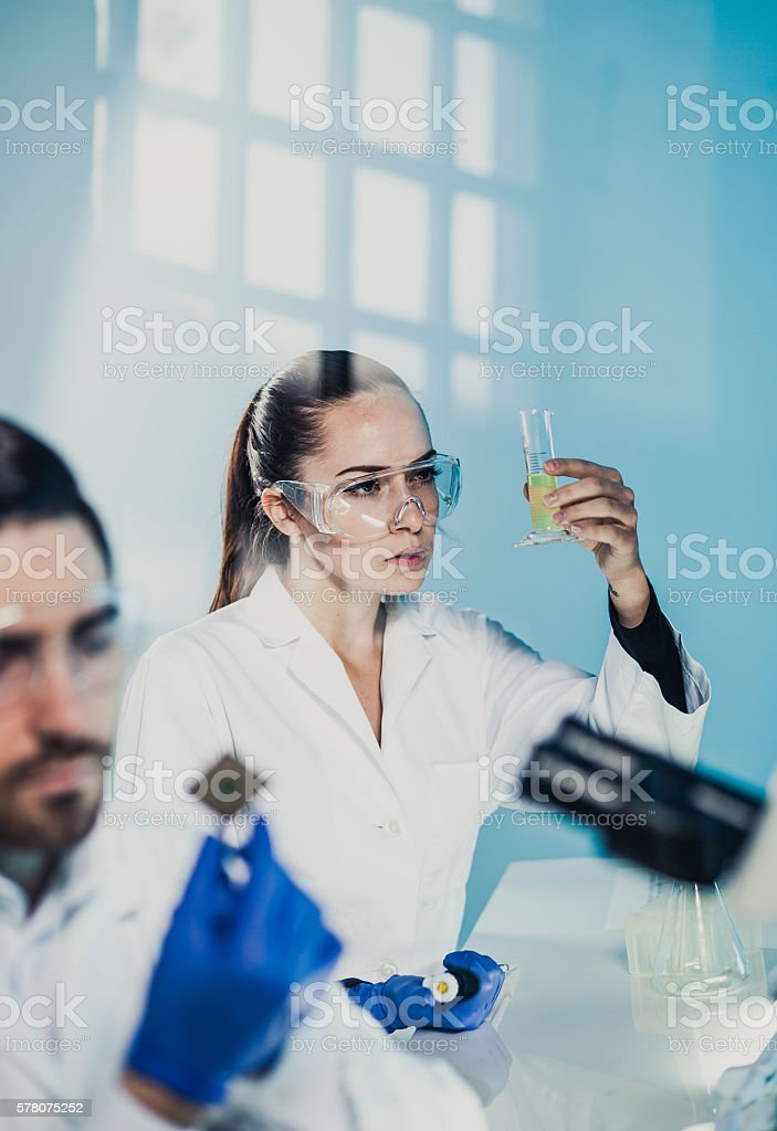 Scientists Looking at the Measuring Cylinder stock photo