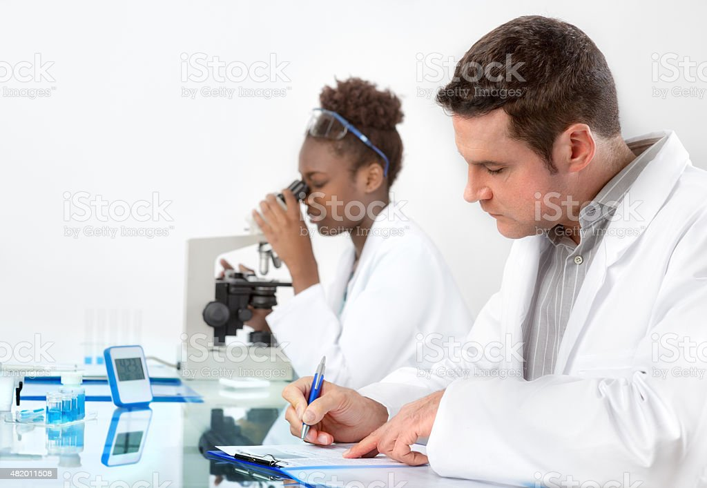 Scientists, male and female, work in laboratory stock photo