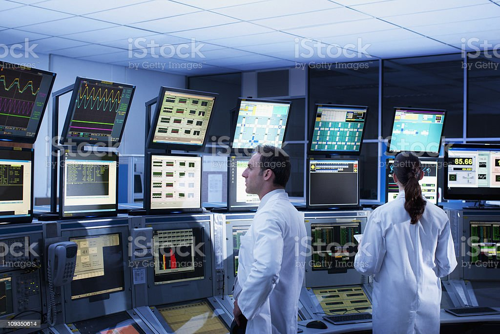 Scientists monitoring computers in control room royalty-free stock photo