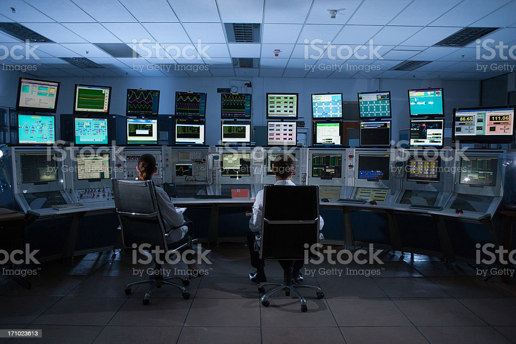 Scientists monitoring computers in control room stock photo