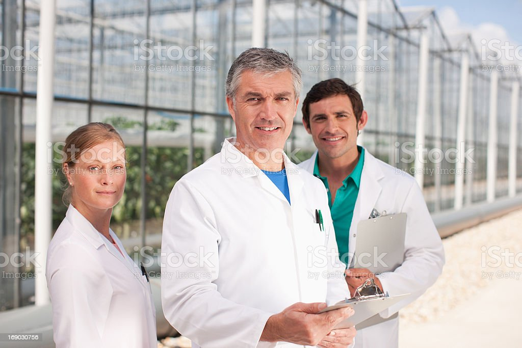 Scientists outside greenhouses royalty-free stock photo