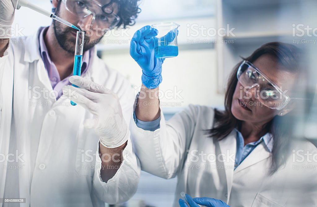 Scientists Pipetting Into a Test Tube stock photo