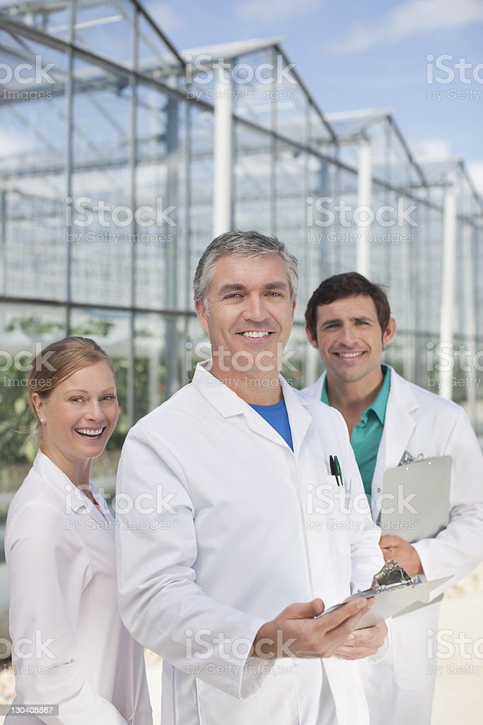Scientists smiling outside greenhouses royalty-free stock photo