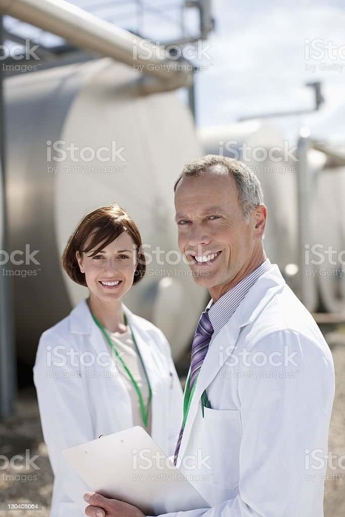 Scientists standing by tanks outdoors royalty-free stock photo