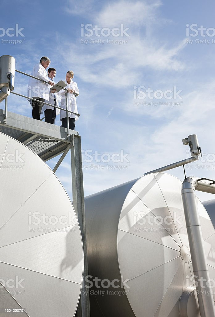 Scientists standing on walkway on tanks royalty-free stock photo