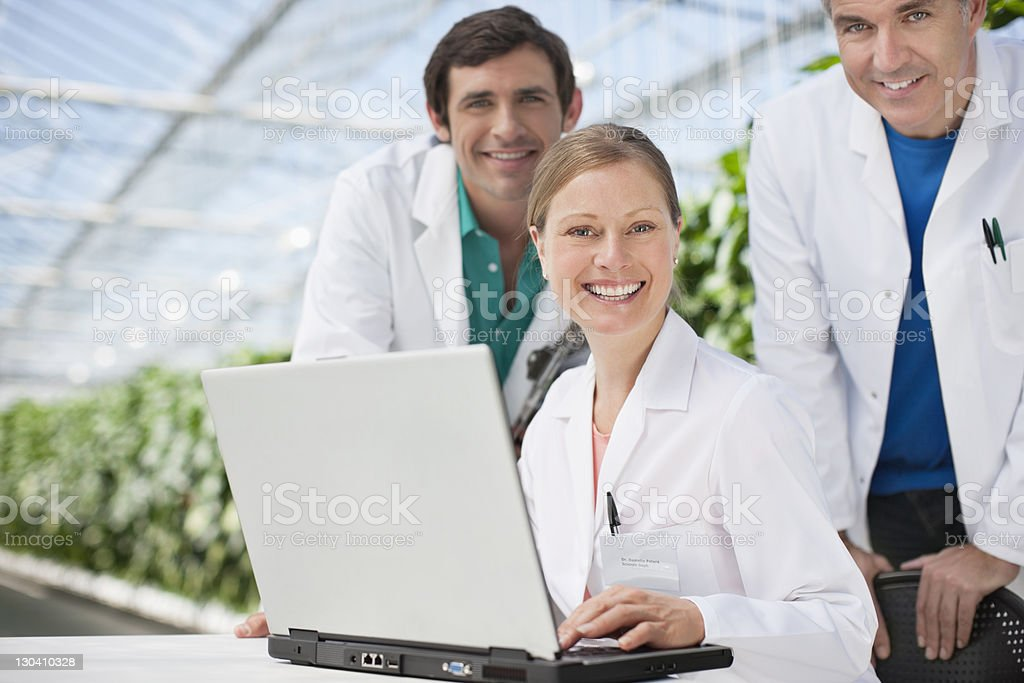 Scientists working on laptop in greenhouse royalty-free stock photo