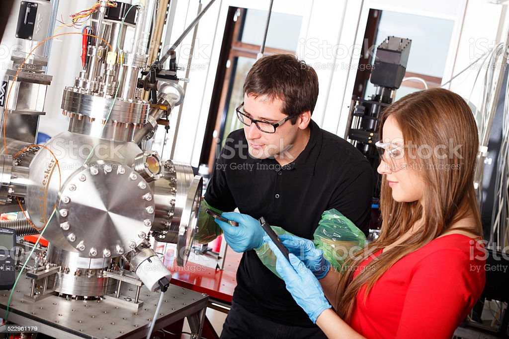 Scientists working with laser deposition chamber stock photo