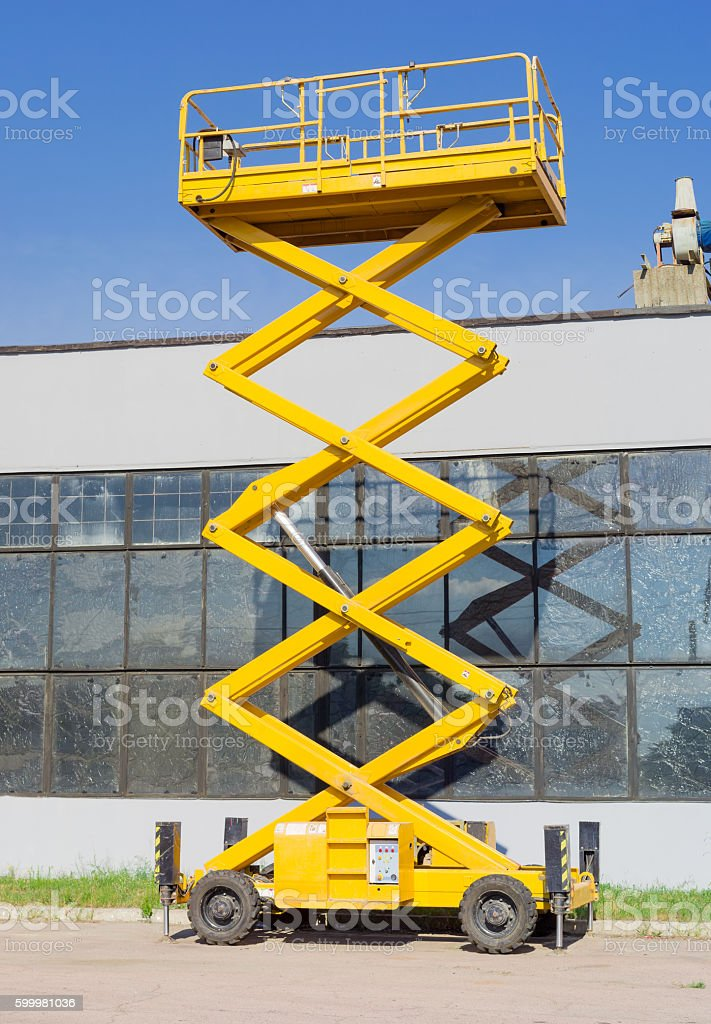 Scissor self propelled lift on the background of industrial buil stock photo