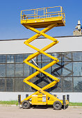 Scissor self propelled lift on the background of industrial buil